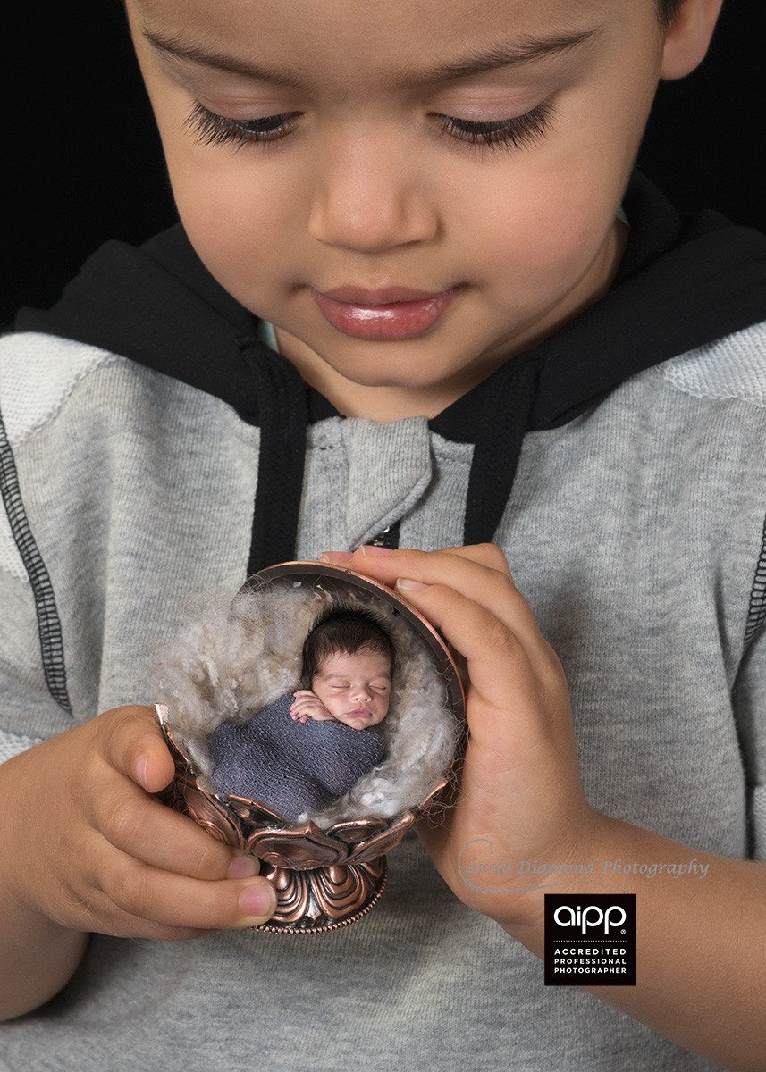 3 year old holding his precious newborn brother in a vase