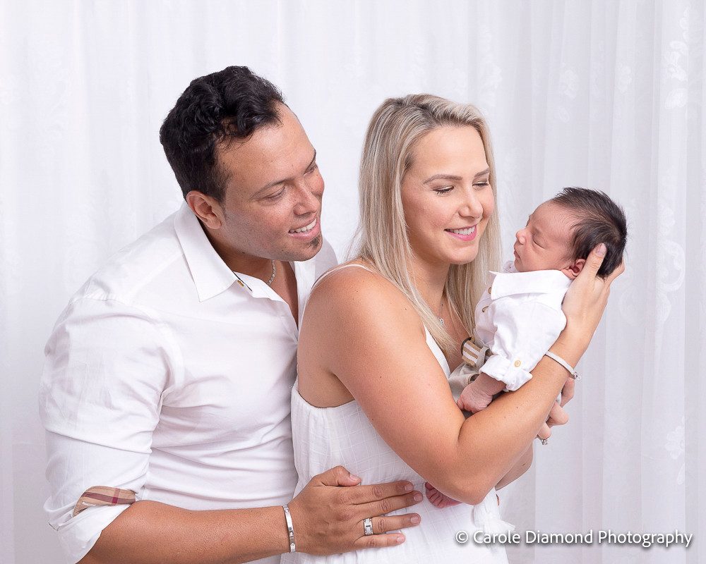 Loving mother holding newborn baby with father looking over her shoulder, in studio newborn photos by Carole Diamond Photography, Sutherland Shire Newborn Photographer.