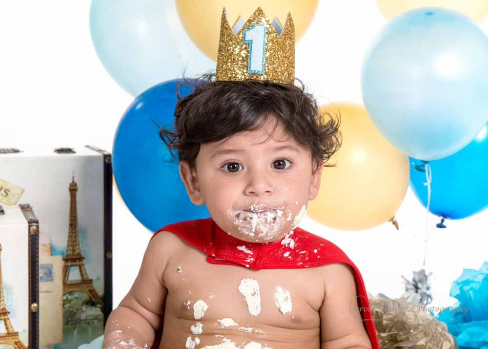 cute little prince with cake over face after his cake smash photo shoot