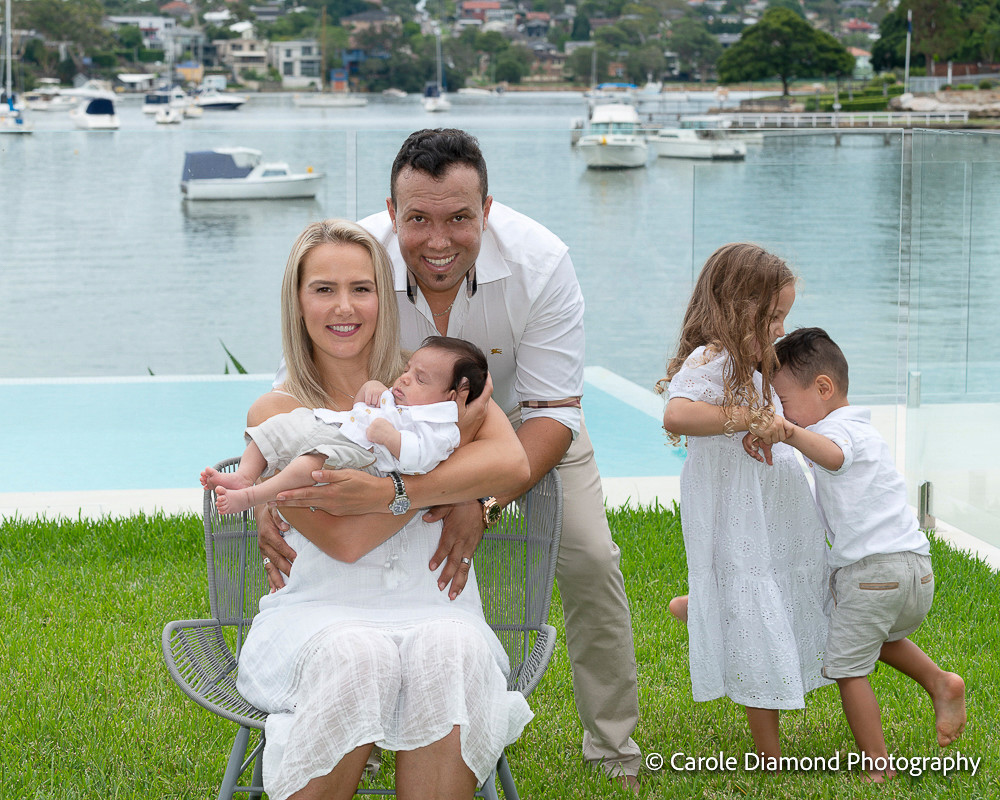 In home family photos taken at this gorgeous clients tennyson point home, their yard is located on the water! what a great view the two older children playing in the back unknowing photo bombing mum and dads newborn photo