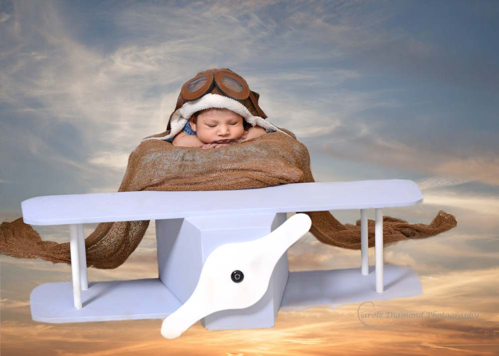 posed sleeping newborn baby in aeroplane