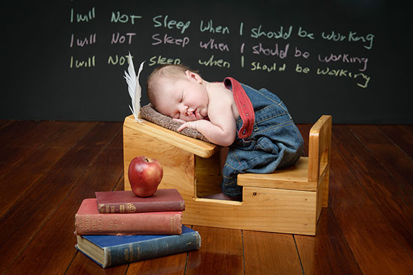 newborn baby sleeping on desk in the background written on blackboard is I will not sleep while working