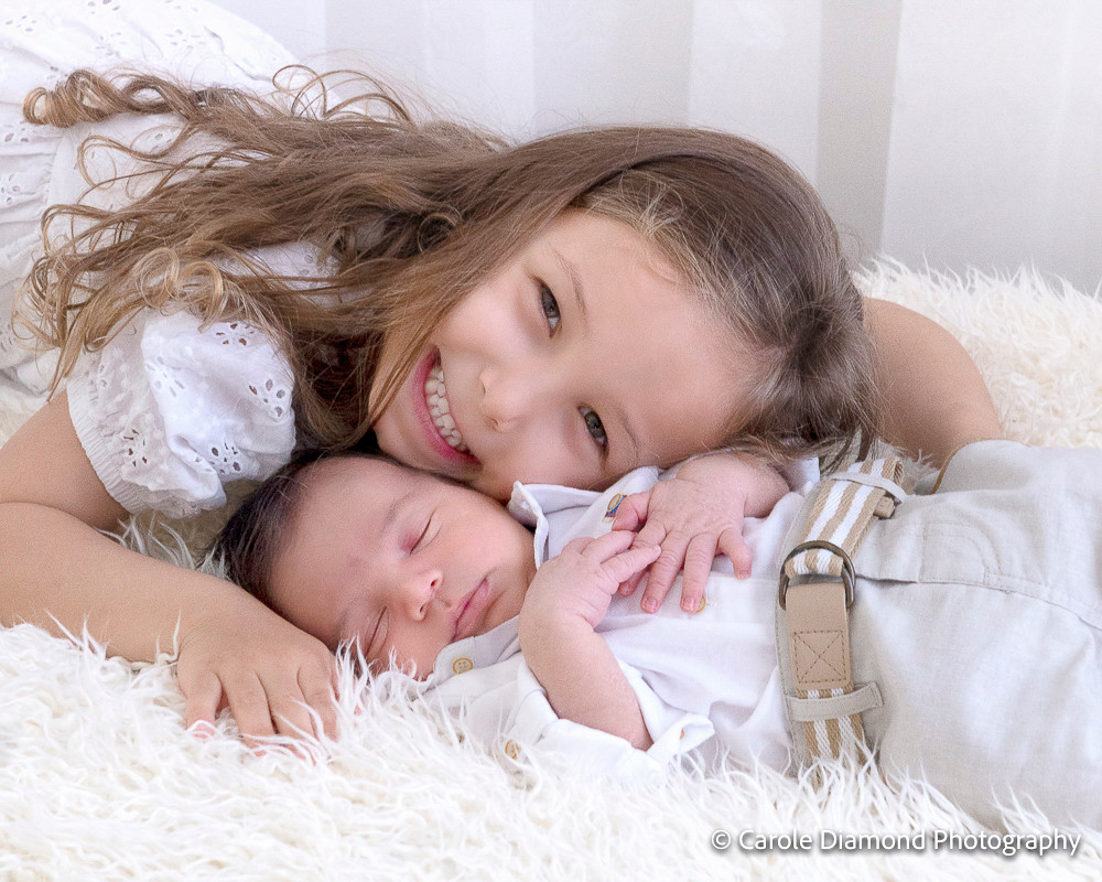 beautiful miss 4 giving lovely cuddles to newborn brother during their in studio photo sitting by Sutherland Shire Photographer Carole Diamond Photography