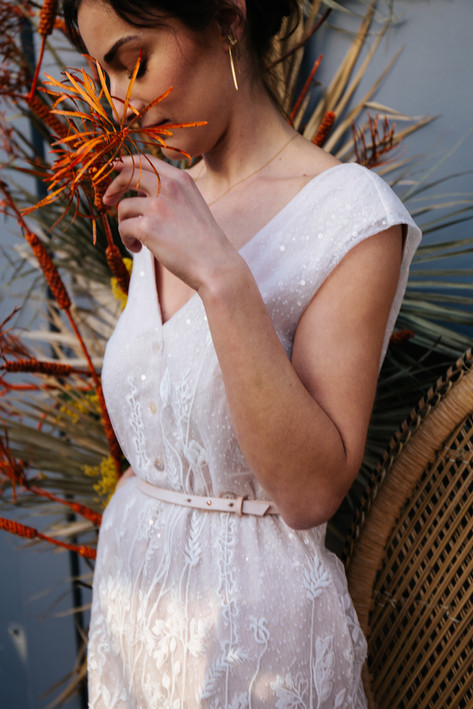 Lace and satin bridal jumpsuit. Featuring mother-of-pearl buttons, a matching leather belt and a detachable tulle overskirt. Bespoke and one of a kind, by Lilli Turner Couture  Photoshoot in collaboration with: Photography: Yara Brouwer Bridal jumpsuit: Lilli Turner Couture Suit: SLFMD Tailoring Location: Vers Hoekse Waard Styling: Lekker Eigenwijz Flowers: Meester in Bloemen Stationary: Cotton Bird Cake: Cheffi's Pastries Jewelry: Maja Lava Hair & make-up: Cassidy Bonsink Models: Myrthe Hogeterp & Amir Kasanrokijat