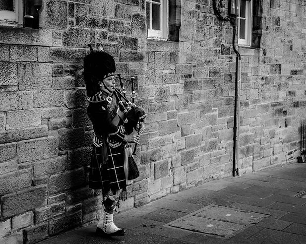 Canva - Person Using Bagpipes Near Wall