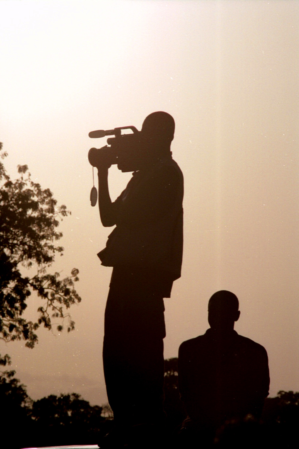 While on a 5 week trip to Africa, I was given an opportunity to work with the Gambian Television and Radio Service. We traveled to the President's home and shoot a festival that I can't quite recall. While shooting, I saw one of the cameramen standing on top of the truck shooting with his camera and I saw the silhouette of him and his camera and I thought it would be a great shot.