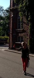 Mónica Ramón Ríos caminado por una calle en cuyo fondo hay un edificio de ladrillo antiguo.