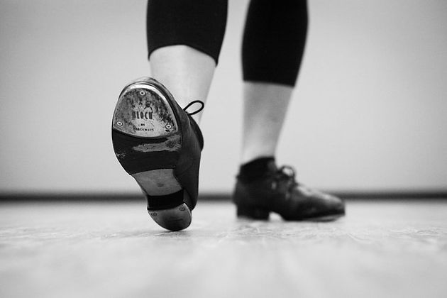 A person that is about to tap dance in black and white picture