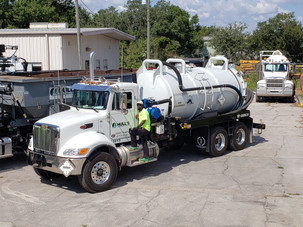 worker poses with new liquid vacuum truck at Hull's Environmental Services Tampa location