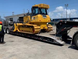 new John Deere 700k dozer being unloaded for Hull's Environmental Services