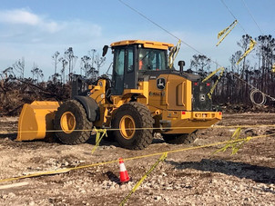 front-end loader working in a field for Hull's Environmental Services