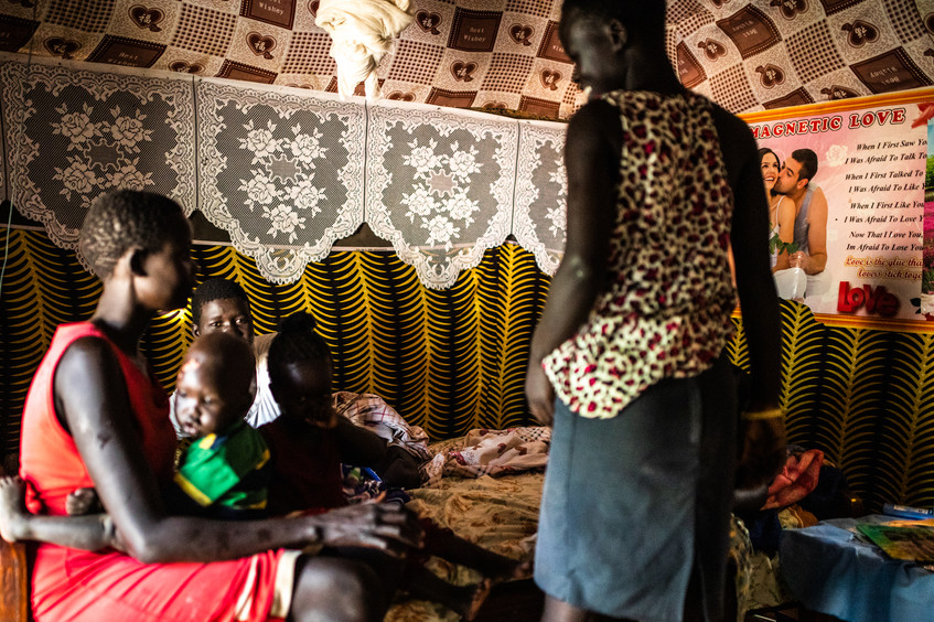 South Sudanese family. It's common that only women and children flee from homelands. Houses are small and made of clay and hay. Five persons might sleep in one bed.