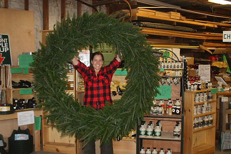 Woman wearing red flannel shirt holds a wreath as tall as she is.