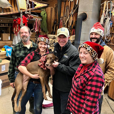 Five people standing.  A woman wearing a santa hat holds a brown dog with a bow on its collar.