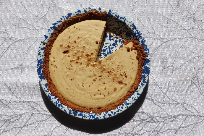 A pie with a single slice removed in a blue and white speckled pie pan.  The pan is on a patterned white tablecloth.