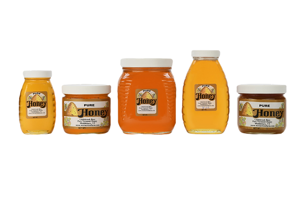 Five glass honey jars of different sizes with a white background.