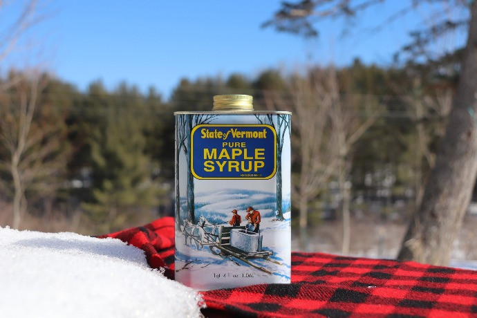 A metal container on top of a red and black checked tablecloth.  The metal container has a picture of a horse drawn sled.  Yellow letters on a blue background read State of Vermont: Pure Maple Syrup.