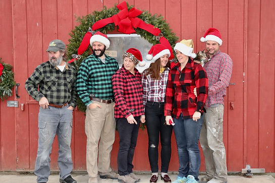 Six people stand in front of a red barn with a wreath.