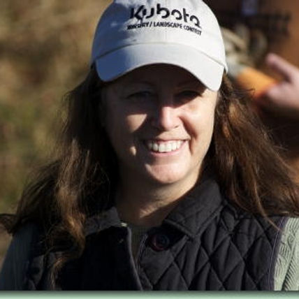 Face of a woman wearing a baseball cap with long brown hair.