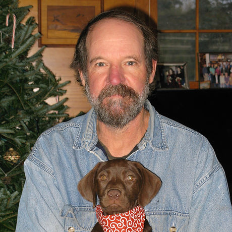 Man in a blue shirt holds a brown puppy with bandana.