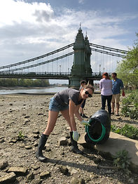 family volunteering picking up plastic litter by the river Thames