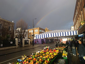 Image of North End Road market featuring a rainbow over a grey sky