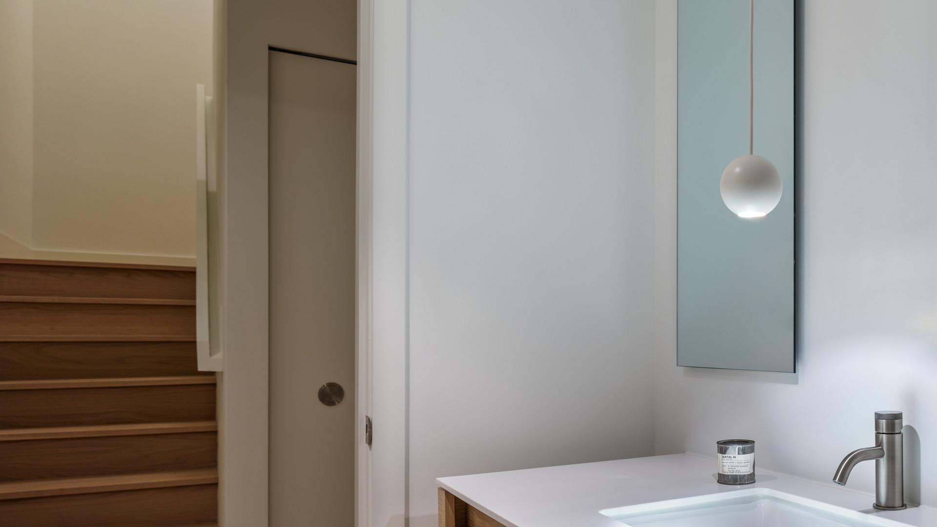 modern powder room with davide groppi pendant by untitled design agency