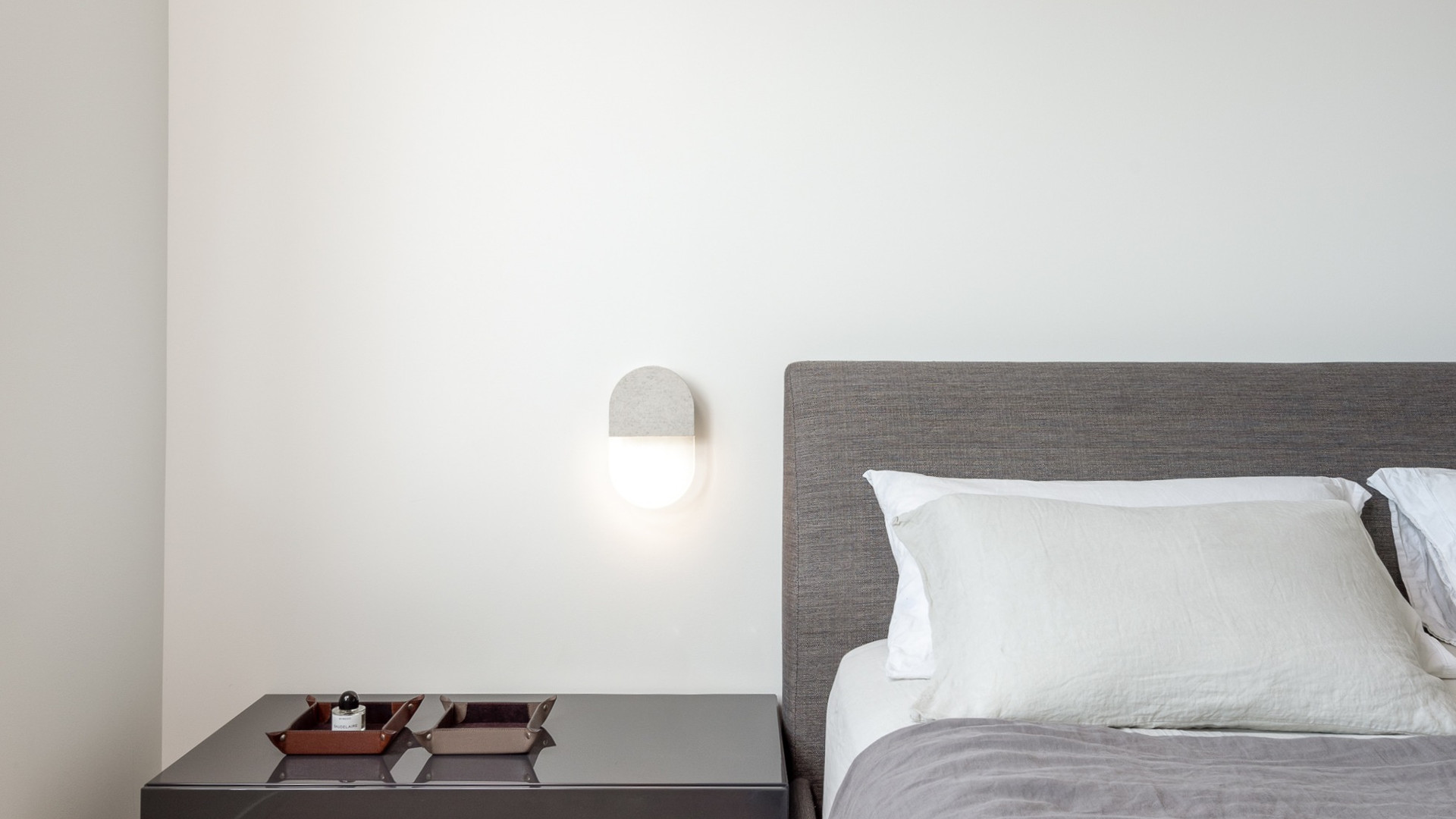 modern bedroom with andlight slab sconce by untitled design agency