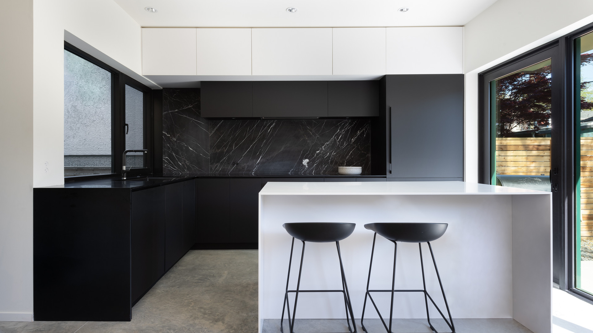 modern black and white kitchen with marble backsplash and hay stools by untitled design agency