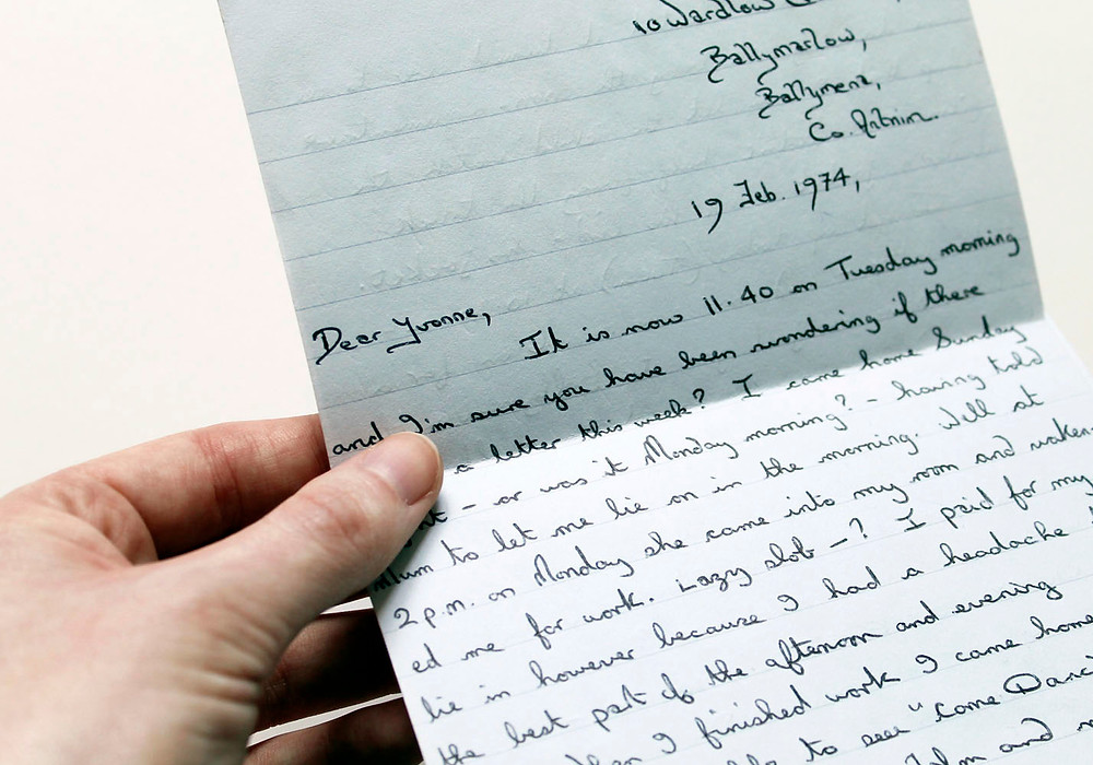 A hand holding a small handwritten letter dated 1974.