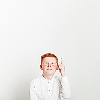 ginger-boy-pointing-up-towards-copyspace