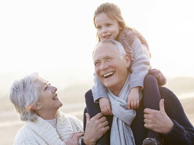 Насмеан дедо ја носи внуката околу врат, а бабата насмеана ги гледа