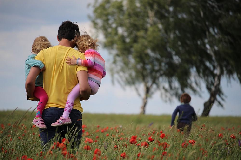 Таткото во раце ги носи двете мали ќерки, а пред него на полјаната трча поголемиот син
