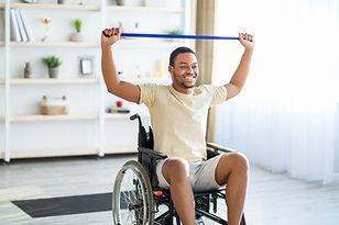 happy-black-disabled-man-in-wheelchair-doing-exerc-JA54JBT-min.jpg
