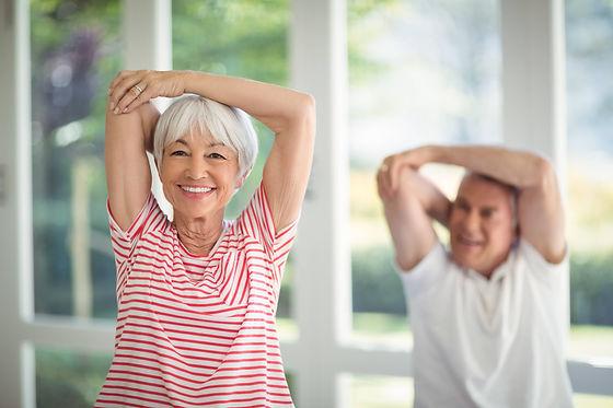 senior-couple-performing-stretching-exercise-at-ho-UBPULGF-min.jpg