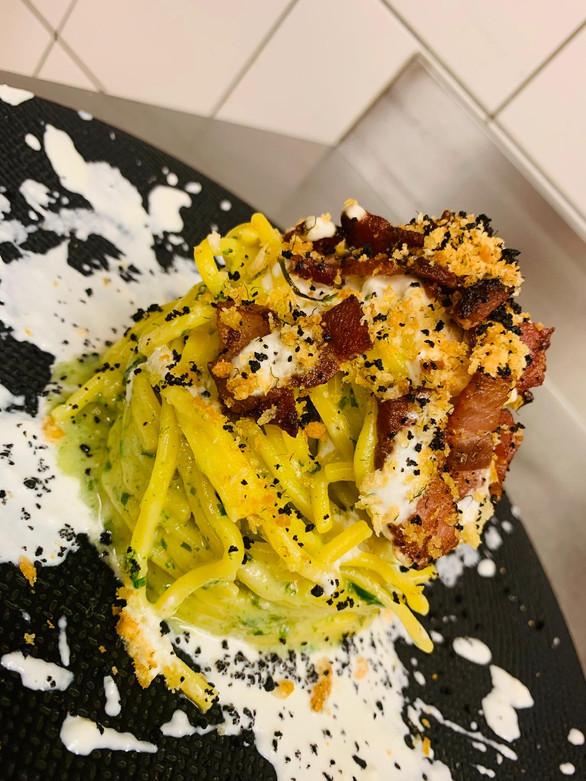 Spaghetto con pesto di rucola, speck croccante, burrata e polvere di olive