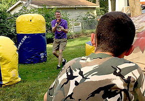 Austin Dasher dodges foam bullets during a Nerf battle with his father, Eric.
