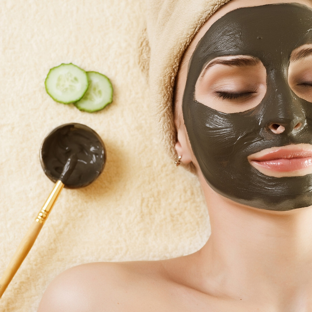 woman laying down with clay facial mask