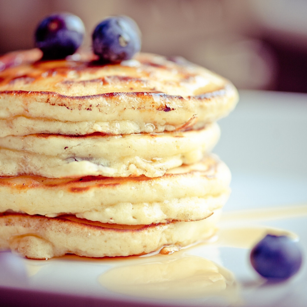A stack of blueberry pancakes with maple syrup on it