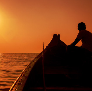 A boatman in his ferry boat looking at sunset in Om Beach, Gokarna, Karnataka.