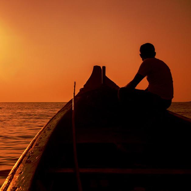 A boatman in his ferry boat looking at sunset in Om Beach, Gokarna, Karnataka.