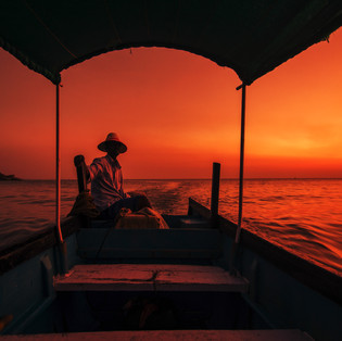 A boatman in his ferry boat at Sunset in Om Beach, Gokarna, Karnataka.