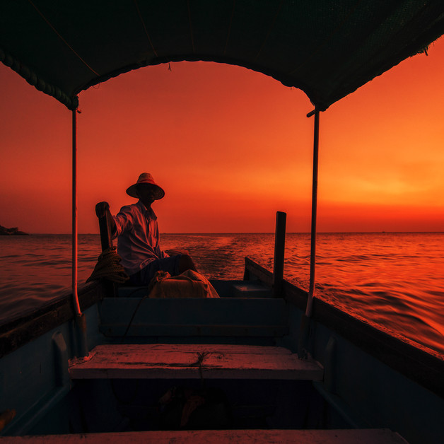 A boatman in his ferry boat at Sunset in Om Beach, Gokarna, Karnataka.