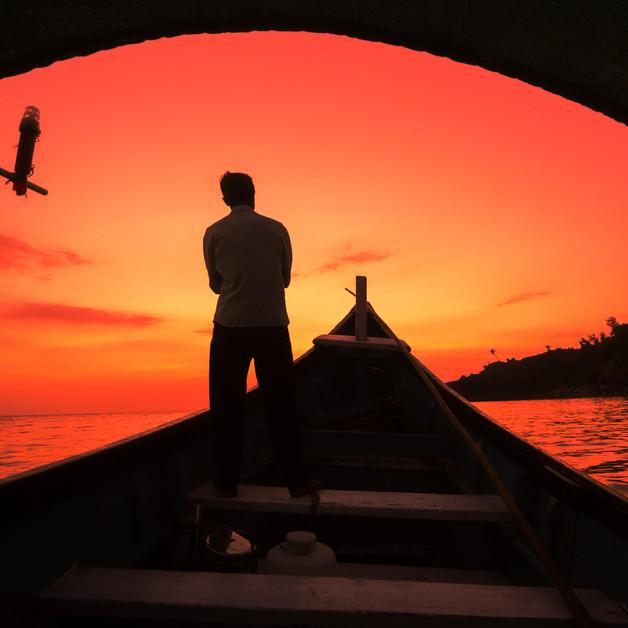 Silhouette of a boatman in his ferry boat at Sunset in Om Beach, Gokarna, Karnataka.