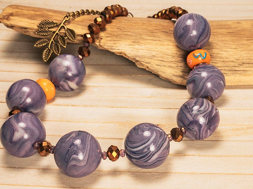 Necklace with chunky swirly purple beads contrasted with smaller orange glass be