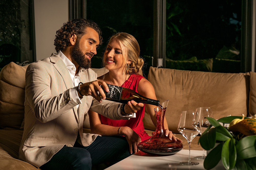 Young couple decanting a bottle of red wine purchased from Yahyn for valentines day