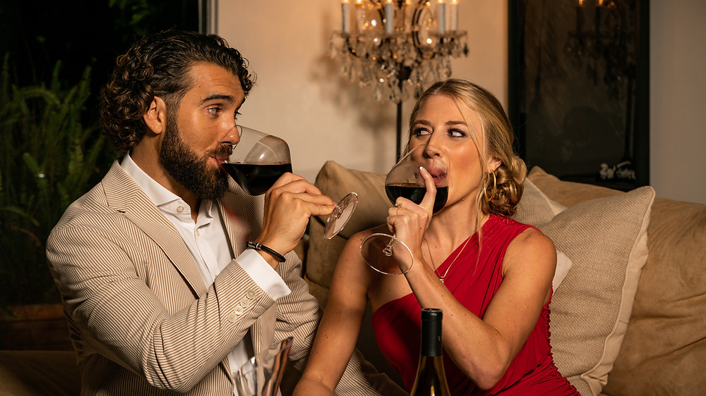 Young Couple in love sharing a glass of red wine bought from Yahyn on valentines day.