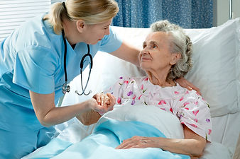 photo of nurse assisting elderly patient in bed