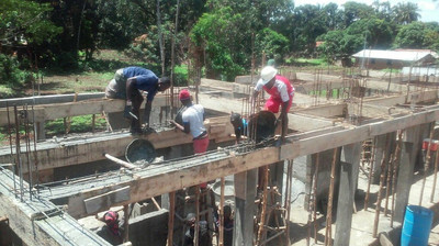 Pouring footings for the new school's second floor slab.