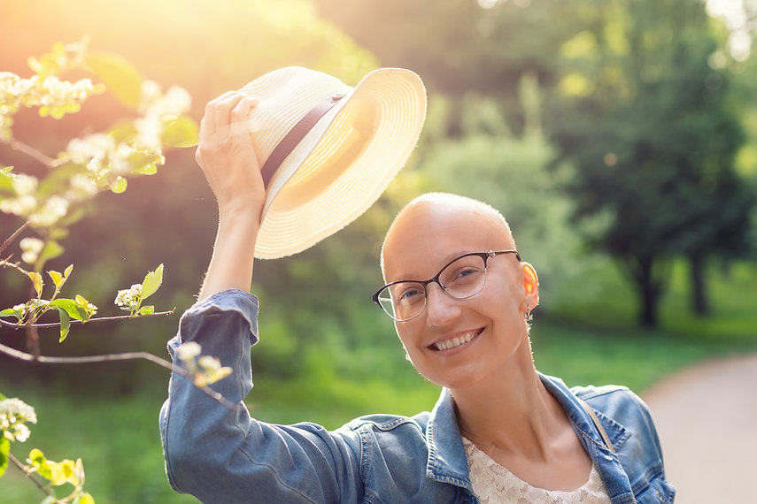Happy young caucasian bald confident hipster woman take off hat and enjoying life after su